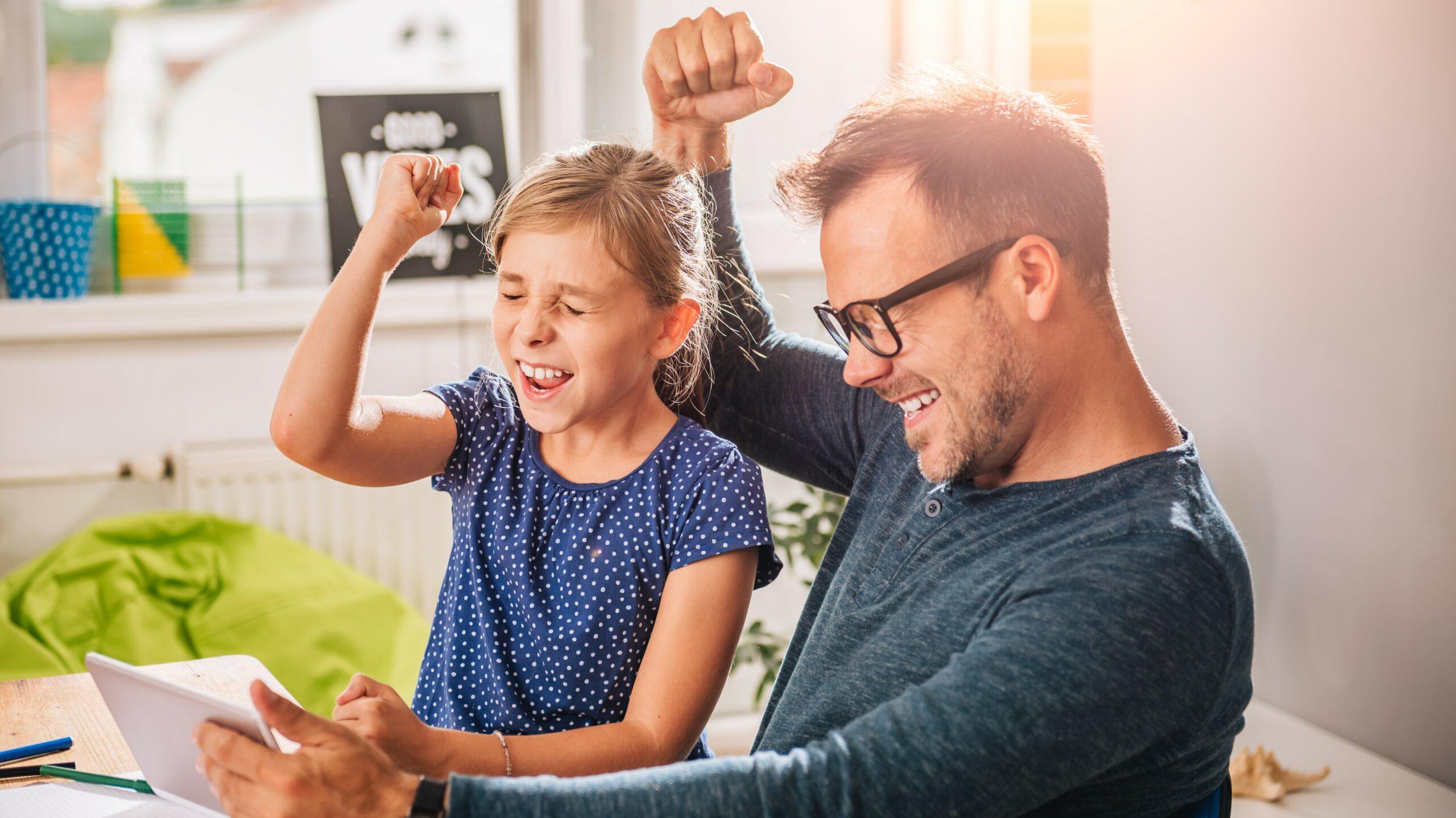Father And Daughter Cheering during playing game on tablet